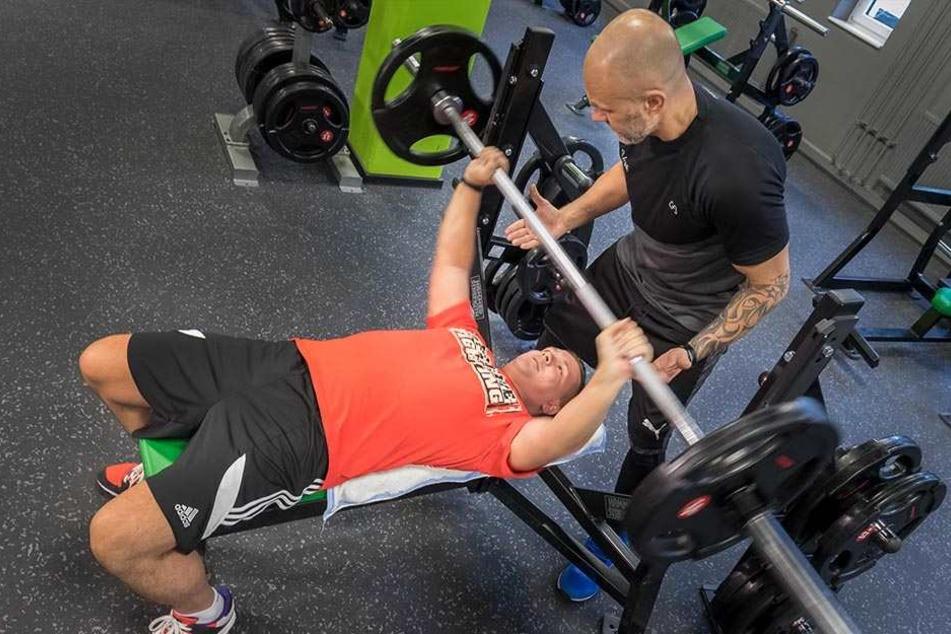 Mit Vorsätzen Gewichte stemmen: Robert Maintok (30) mit Trainer Vadim Istomin (46) beim Bankdrücken im Studio Fit/One.