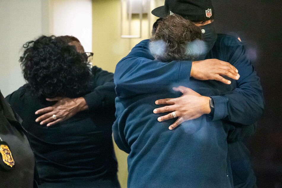 People hug after learning that their loved one is safe after a person shot and killed 8 people inside a FedEx building late Thursday night.