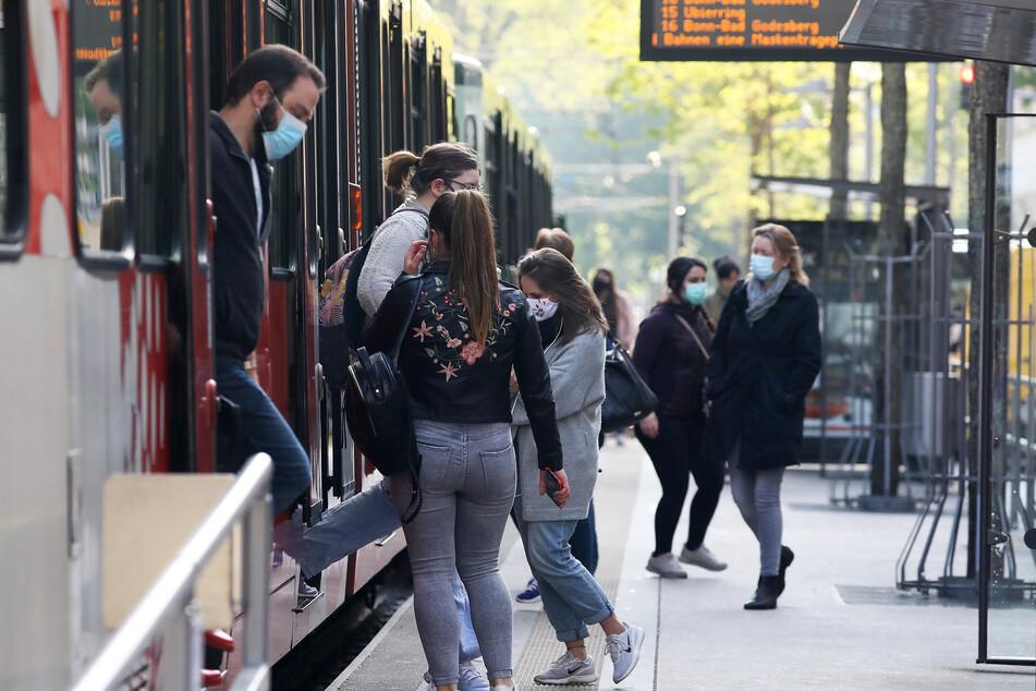 Fahrgäste steigen mit Mundschutz aus und in eine Stadtbahn am Neumarkt (Archivbild).