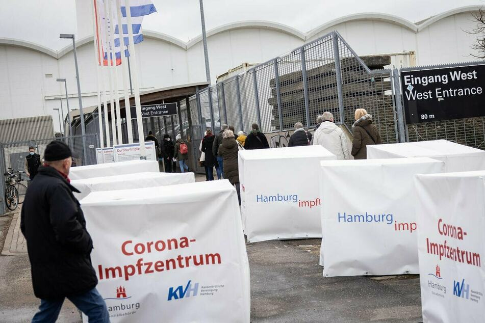 Menschen stehen vor dem Corona-Impfzentrum an den Hamburger Messehallen.