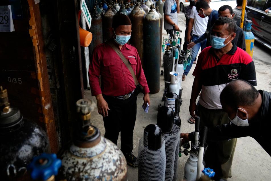 Menschen stehen vor einer Ladestation an, um Sauerstoffflaschen erneut zu befüllen.