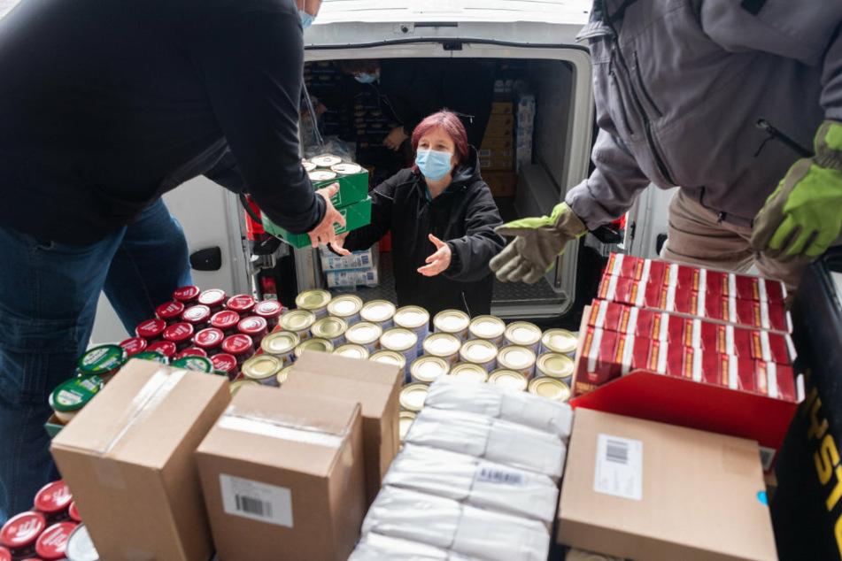 Die Mitarbeiter der Tafel verladen mit Mundschutz Lebensmittel.