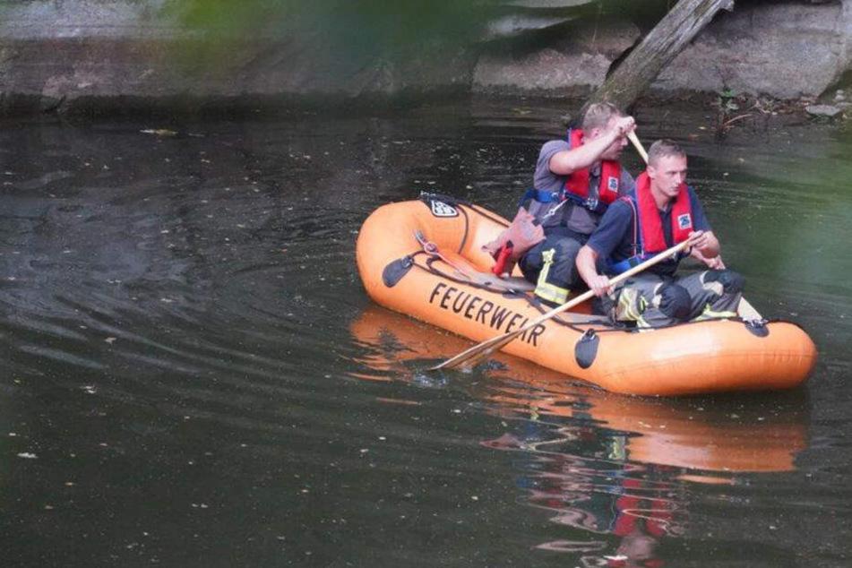 Mit einem Boot sind Feuerwehrleute auf dem Gewässer unterwegs.