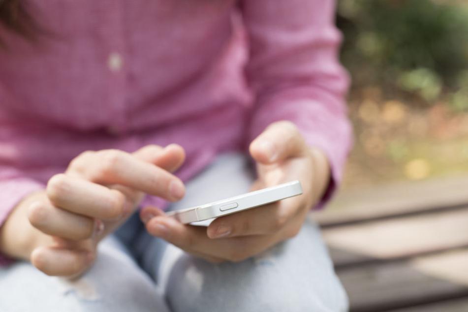 Ein Kind hält ein Smartphone in der Hand. (Symbolbild)