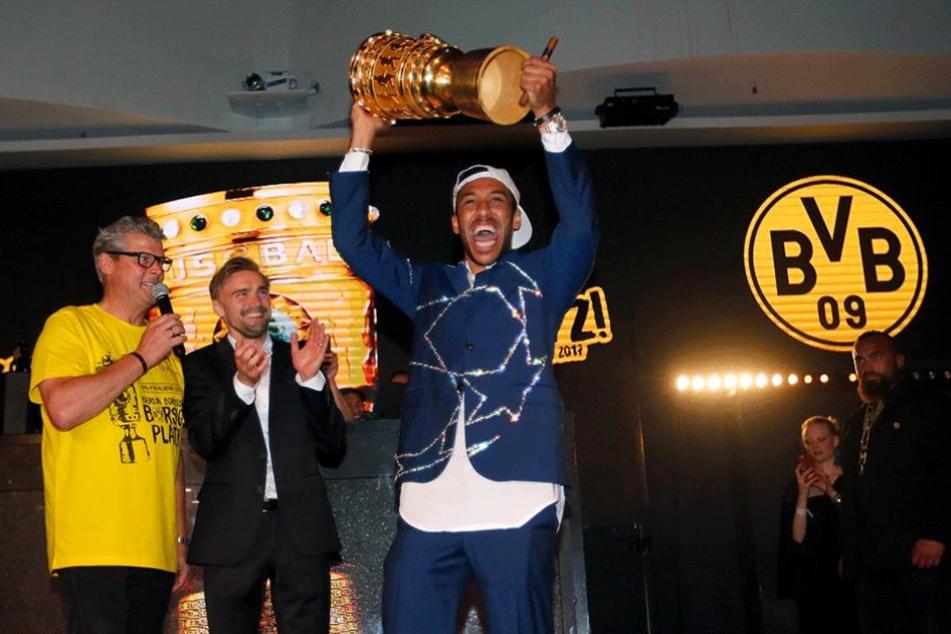 Pierre-Emerick Aubameyang zeigt auf der Siegesfeier den Pokal.