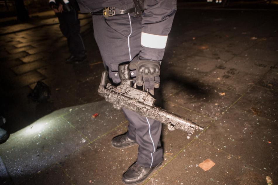 Ein Polizist hält eine geschmolzene Maschinenpistole in der Hand.