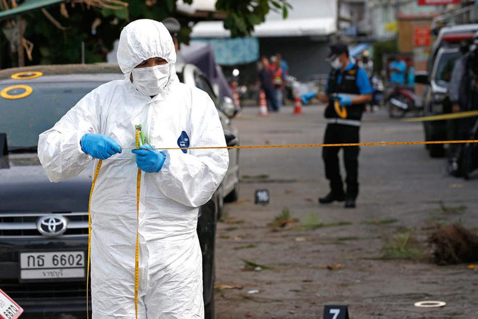 Forensiker und Polizisten sperren den Tatort ab und sichern Spuren.