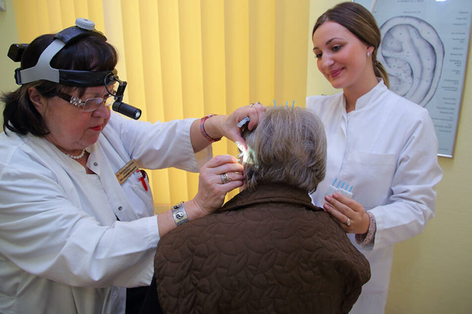 Mit Fingerspitzengefühl setzt die Chef-Allergologin der Uniklinik, Dr. Bettina Hauswald, die Akupunktur-Nadeln punktgenau  am Ohr ihrer Patientin. Doktorandin Henriette Scheibner (24, r.) assistiert.