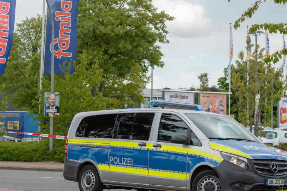 Ein Polizist geht mit einem Bombenspürhund in den Famila-Supermarkt in Reinbek bei Hamburg.