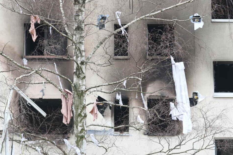 Eine Birke gegenüber des Plattenbaus hängt nach der Explosion voller Kleidungsstücke. Auch ein Fensterrahmen ist unten links zu erkennen.
