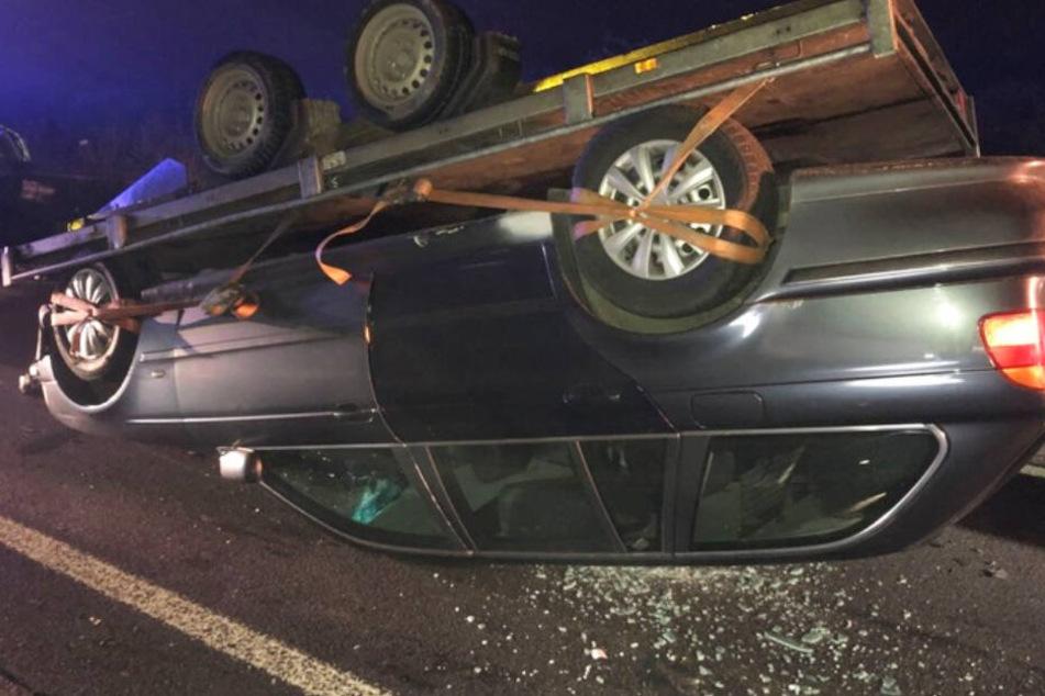 Der transportierte BMW liegt mitsamt Hänger auf dem Dach.