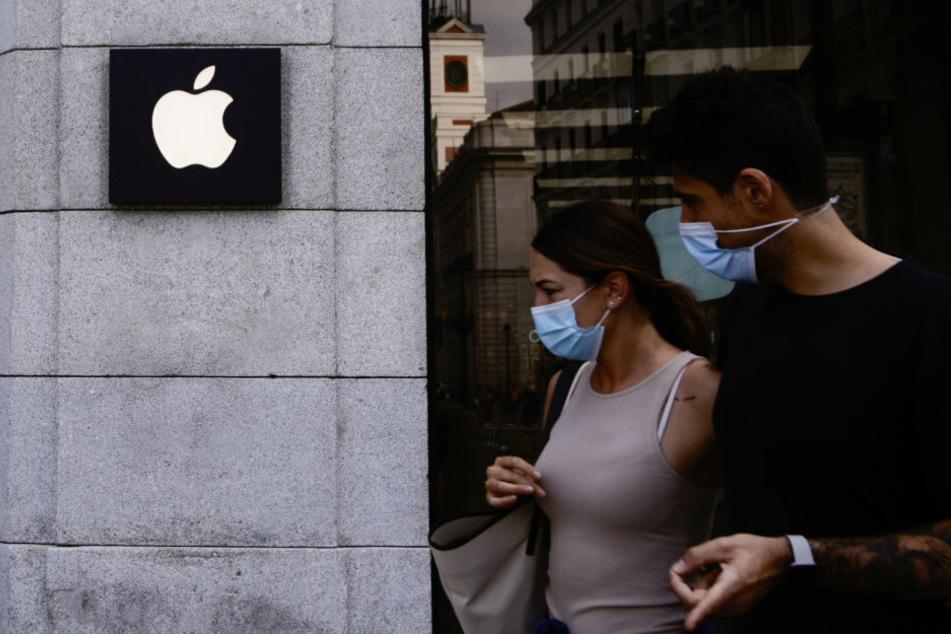 Zwei Leute mit Mundschutz gehen vor einem Apple-Laden in der Innenstadt von Madrid vorbei.