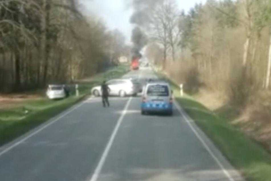 Ein Fahrer steigt aus seinem Auto aus, um bei dem Unfallfahrzeug im Straßengraben Erste Hilfe zu leisten. Ein anderes Fahrzeug wendet und entfernt sich.