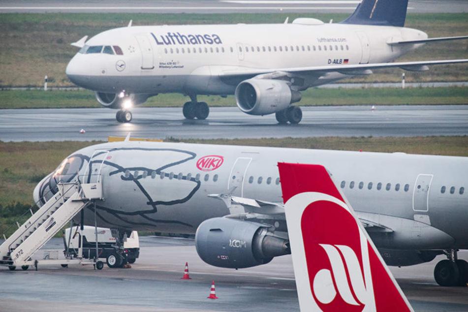 Ein Flugzeug der Fluggesellschaft Lufthansa rollt auf dem Flughafen Düsseldorf auf dem Vorfeld an Flugzeugen der Fluggesellschaften Niki und Air Berlin vorbei.