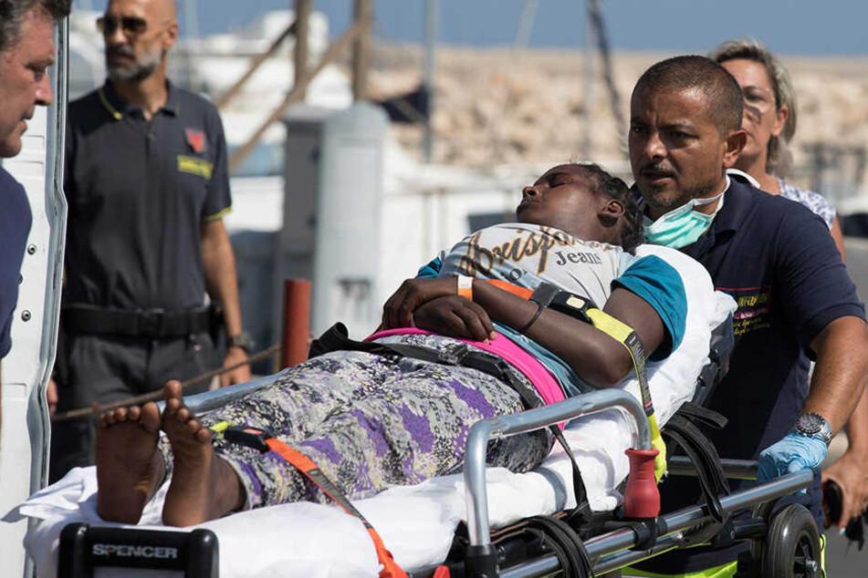 Eine Frau wird auf einer Bahre getragen, nachdem sie von Bord eines Schiffes der italienischen Küstenwache ging.