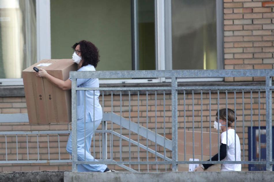 Mitarbeiter des Codogno Krankenhauses tragen Kisten in das Krankenhaus.