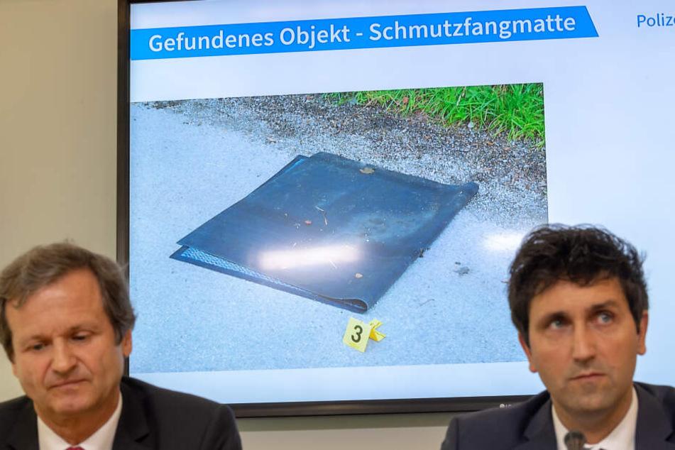 Ken Heidenreich (l), Staatsanwaltschaft München 1 und Josef Wimmer, Leiter Kommissariat 11 zeigen das Beweisstück Fußmatte.