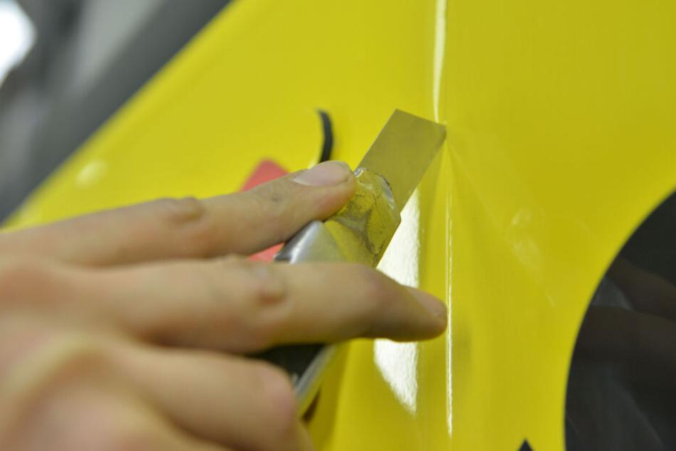 Sauberer Schnitt, saubere Werbung: Damit die Klebefolie optimal aufgetragen werden kann, muss sie zurechtgeschnitten werden - auch um Luftbläschen zu verhindern.