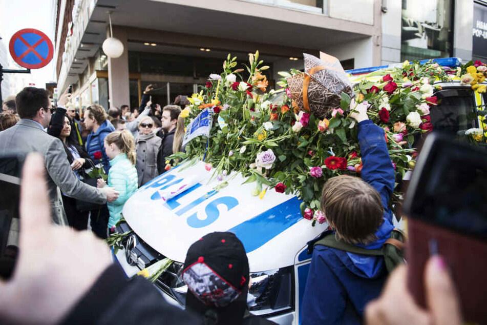 """Nach der """"Liebeskundgebung"""" in Stockholm waren zahlreiche Polizeiautos mit Blumen übersät."""
