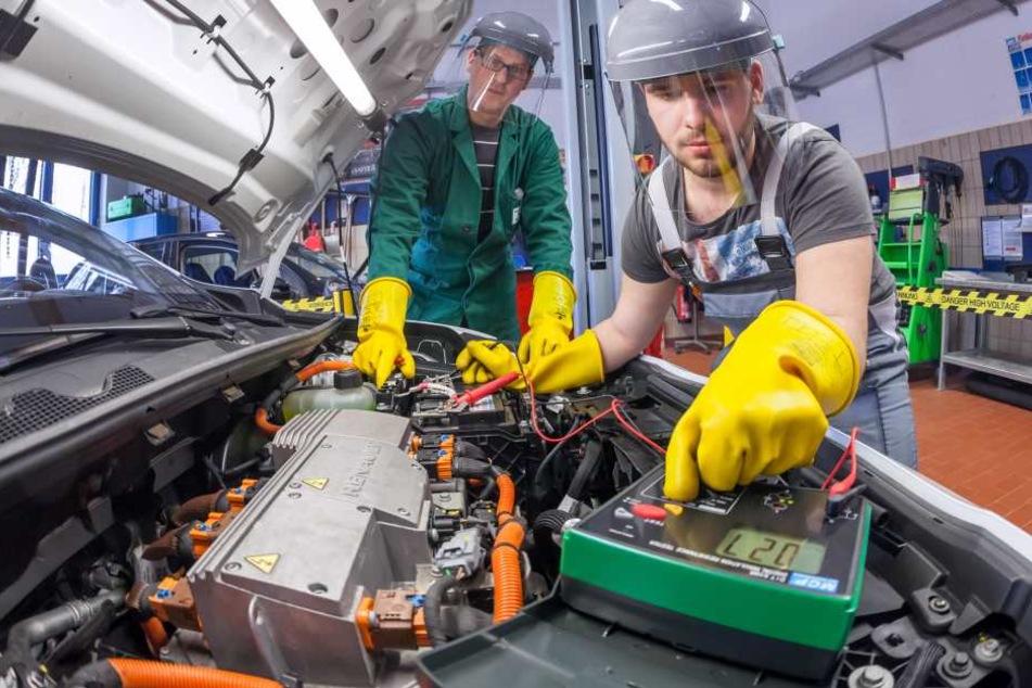 Azubi Marco Beyer (18,r.) und Andy Mosel (31) messen die Spannung an einem  Elektromotor
