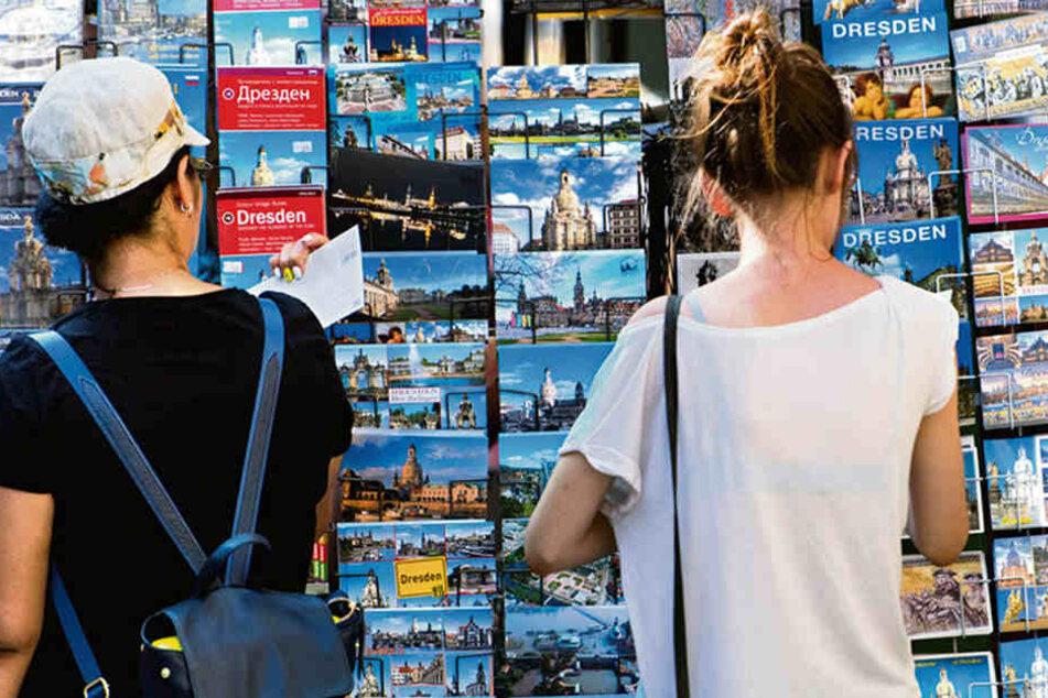 Zwei Frauen sehen sich Postkarten an einem Stand in der Dresdner Altstadt an.