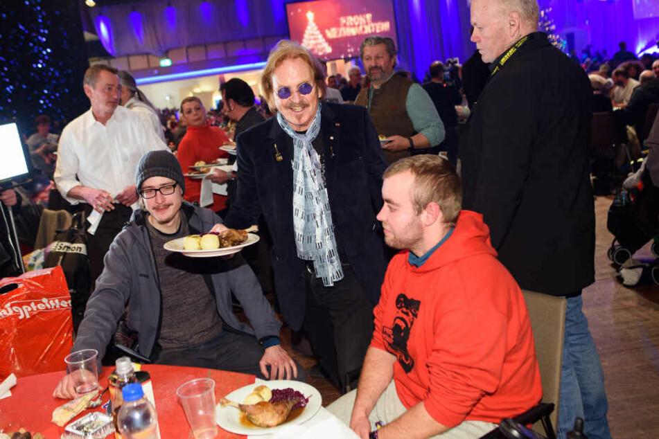 Musiker Frank Zander (M) verteilt bei seinem 25. Weihnachtsfest für Obdachlose und Bedürftige Weihnachtsgans an die Gäste.