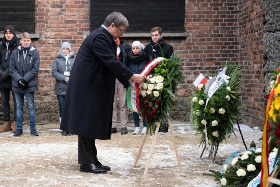 Armin Laschet steht vor einem Gedenkkranz, den Jugendliche aus seiner Delegation zuvor aufgestellt hatten.