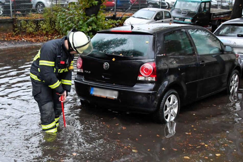 Ein Feuerwehrmann steht knöcheltief im Wasser und versucht den Gulli von Laub zu befreien.