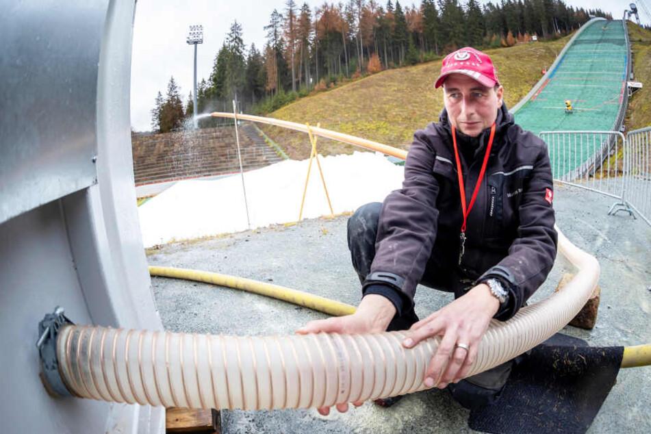 """Techniker Markus Reinert (42) kontrolliert den Schlauch eines Containern, in dem künstlicher Schnee produziert wird - quasi zum """"Zufüttern""""."""