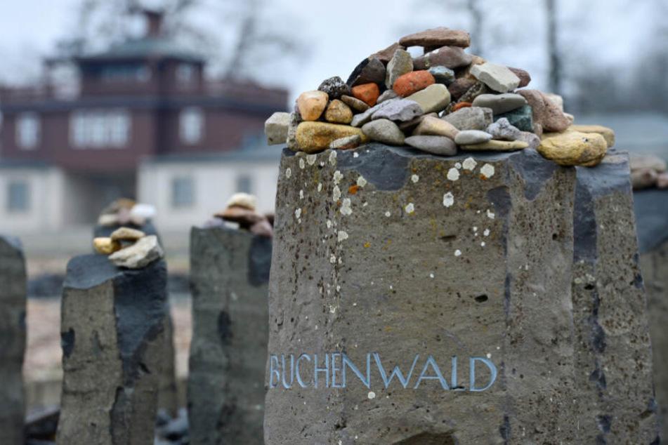 """Kleine Steine liegen im ehemaligen Konzentrationslager Buchenwald auf einem Gedenkstein mit der Aufschrift """"Buchenwald""""."""
