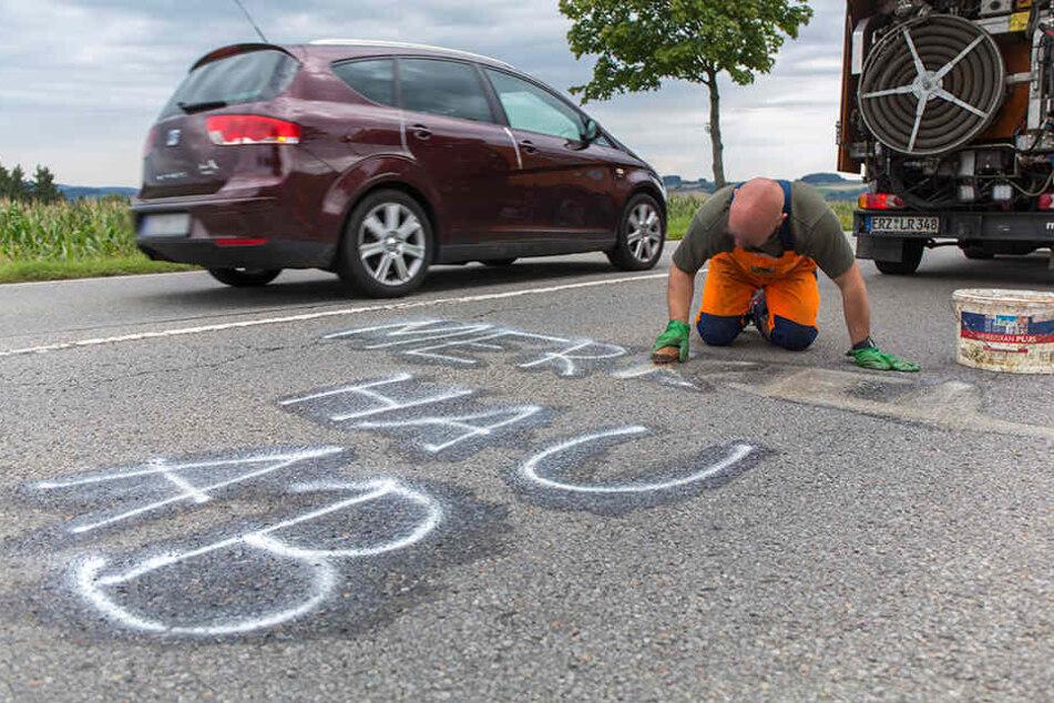 Mitarbeiter der Straßenmeisterei sind derzeit im Einsatz um die Schriftzüge mühevoll in Handarbeit zu entfernen.