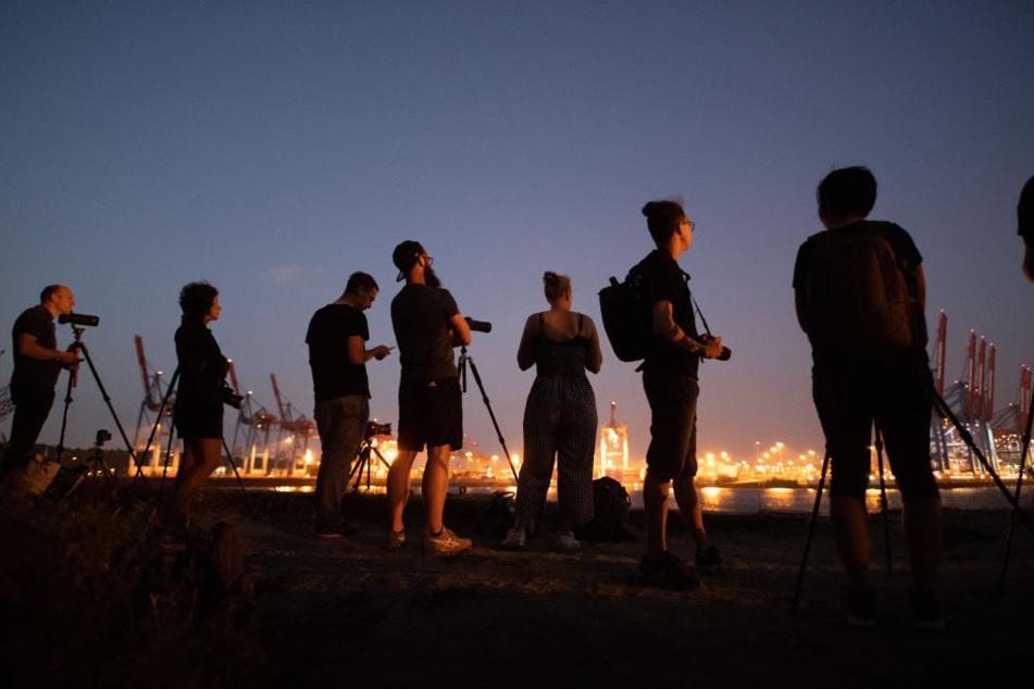 Schaulustige in Hamburg positionierten sich am Hafen, um das perfekte Bild vom aufgehenden Mond zu schießen.