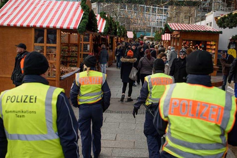 Polizeibeamte gehen über den Weihnachtsmarkt an der Gedächtniskirche auf dem Breitscheidplatz Streife.