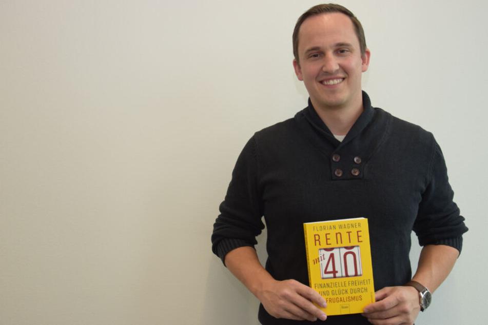 """Florian Wagner hält sein Buch """"Rente mit 40"""" in den Händen."""