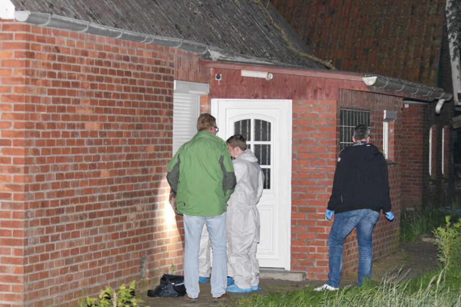 Polizeibeamte untersuchen eine Eingangstür des Hauses, in dem die 31-Jährige tot aufgefunden wurde.