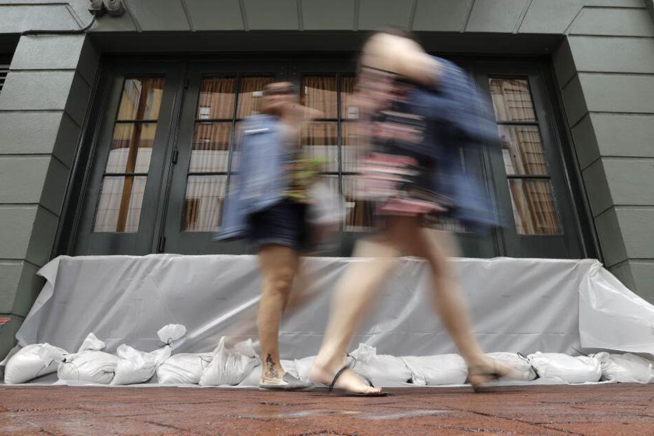 Besucher gehen an Sandsäcken vorbei, die ein Geschäft entlang der Bourbon Street im French Quarter vor dem Tropensturm schützen sollen.