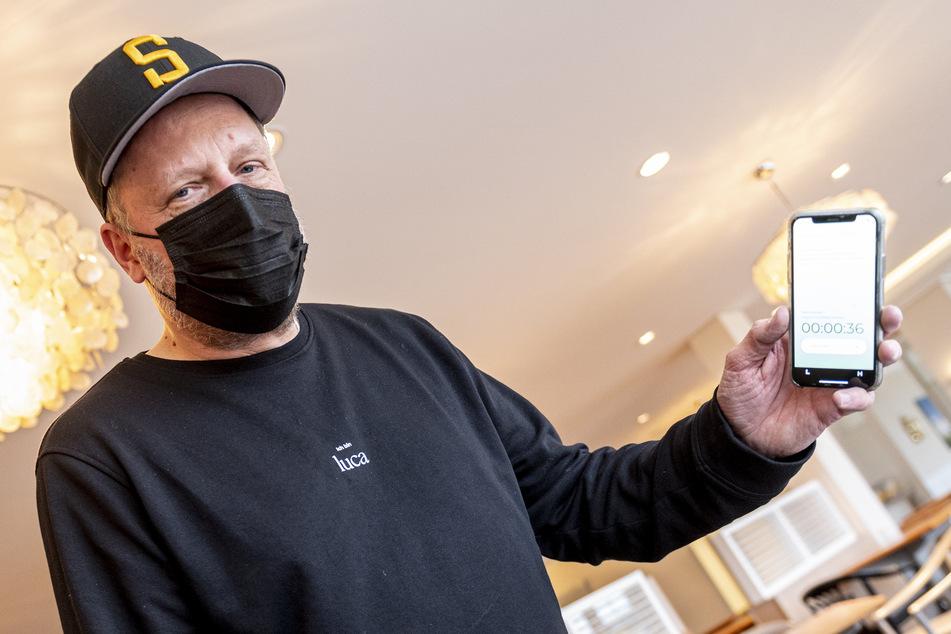"""Rapper Smudo (54) demonstriert auf seinem Smartphone die Funktionsweise der App """"Luca"""", die zur Kontaktermittlung bei Corona-Infektionen entwickelt wurde."""