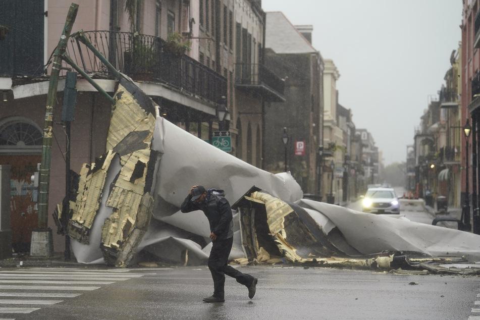 Ein Mann bringt sich in Sicherheit, nachdem ein Teil eines Dachs von einem Gebäude im French Quaeter vom Hurrikan weggeblasen wurde.