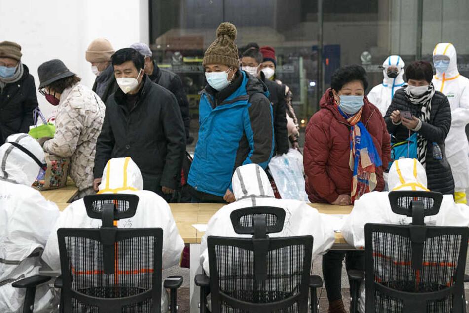 Wuhan: Medizinisches Personal in Schutzanzügen helfen mit dem Coronavirus infizierten Patienten bei ihrer Ankunft in einem Hilfskrankenhaus.