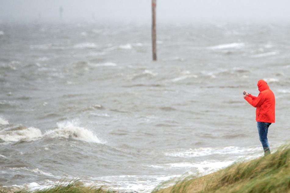 Ein Mann fotografiert an einem Strandabschnitt die peitschenden Wellen der Nordsee.