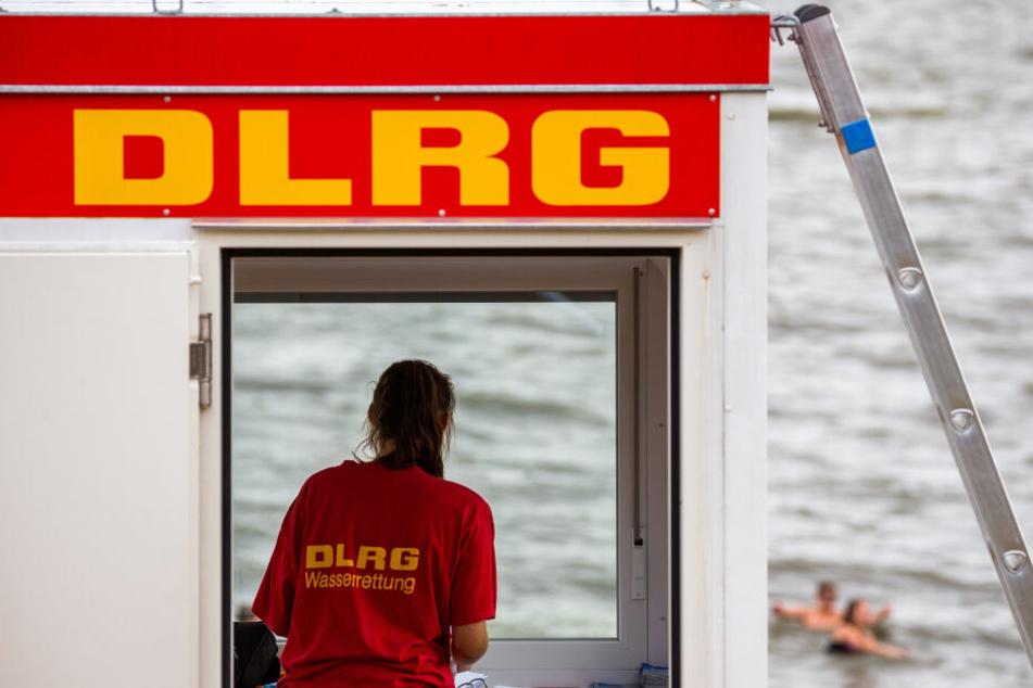 Eine Rettungsschwimmerin der DLRG (Deutsche Lebens-Rettungs-Gesellschaft) steht vor dem Fenster eines Wachturms.