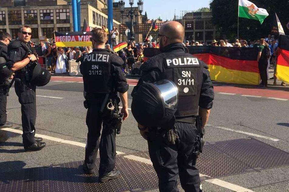 Polizisten stehen bei der PEGIDA- und AfD-Demo vor dem Landtag während des Merkel-Besuchs.
