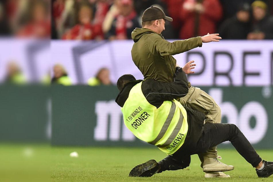 Fußball-Fan flitzt bei Ligaspiel über Feld: Jetzt hat er ein Problem