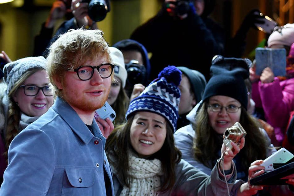 Ed Sheeran mit Fans am roten Teppich.