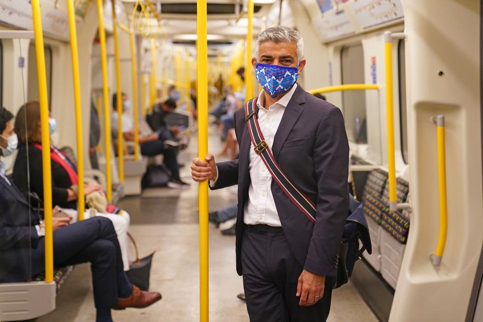 Großbritannien, London: Sadiq Khan, Bürgermeister von London, trägt eine Mund-Nasen-Bedeckung, während er mit der U-Bahn zu seinem Besuch im Londoner Transport Museum fährt.