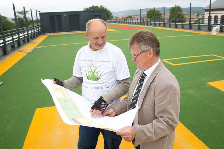 BSZ-Schulleiter Uwe Richter (55, r.) und Andreas Benz (58) vom Spiel- und Sportstätten-Service auf dem frisch verlegten Kunstrasen des Dach-Sportplatzes.