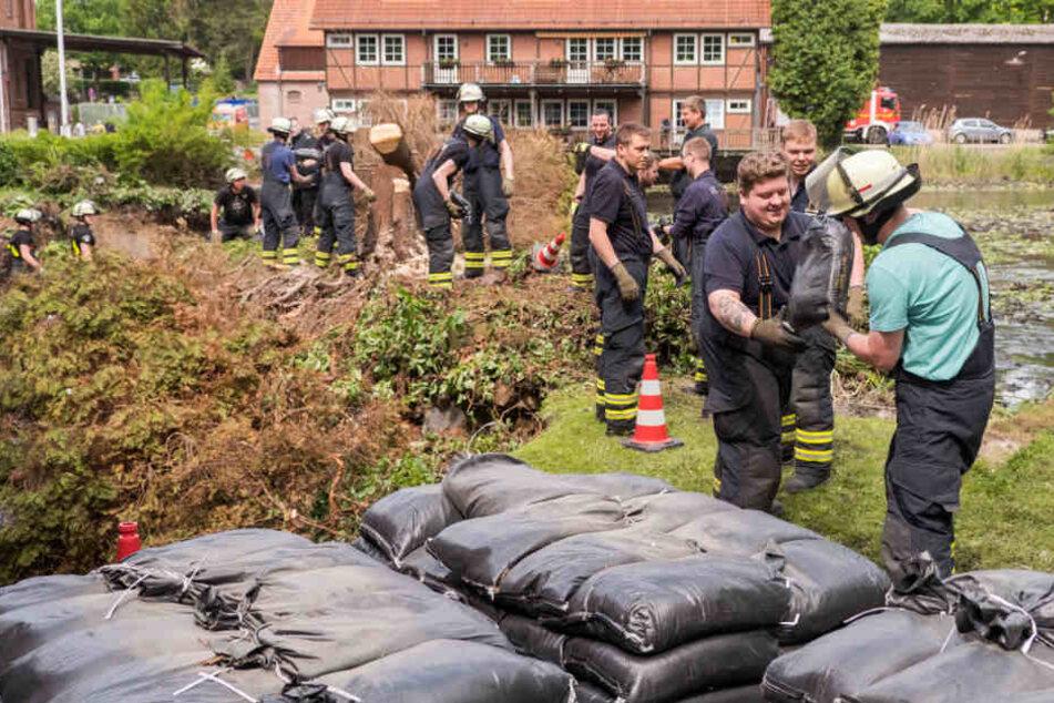 Auch einen Tag nach dem Unwetter verlegen Feuerwehrleute in Kirchsteinbeck tausende Sandsäcke.