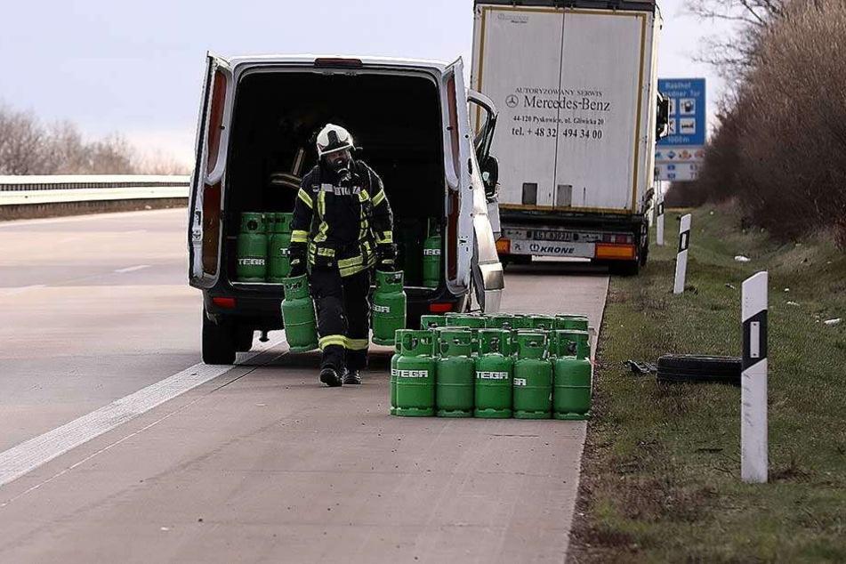 Ein Feuerwehrmann lädt die Gasflaschen aus dem verunglückten Transporter.