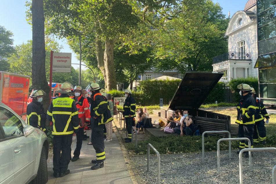 Fahrgäste sitzen neben dem Notausstieg an der Rothenbaumchaussee, nachdem sie von der Feuerwehr evakuiert wurden.