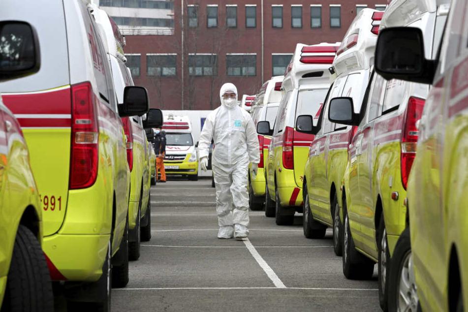 Ein Rettungssanitäter geht in einem Schutzanzug an Krankenwagen vorbei.